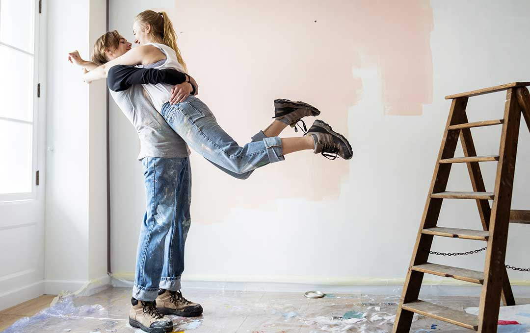 Young couple embracing next to ladder
