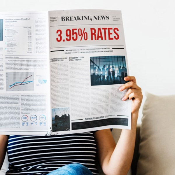 Woman sitting on couch reading newspaper about 3.95% mortgage rates
