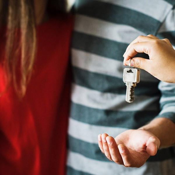 Young couple being handed a key to their brand new home