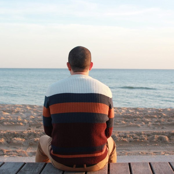 Back of man sitting, looking towards the horizon