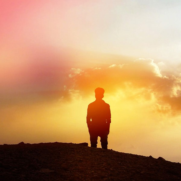 Silhouette of a man on a mountain, looking at clouds in the distance