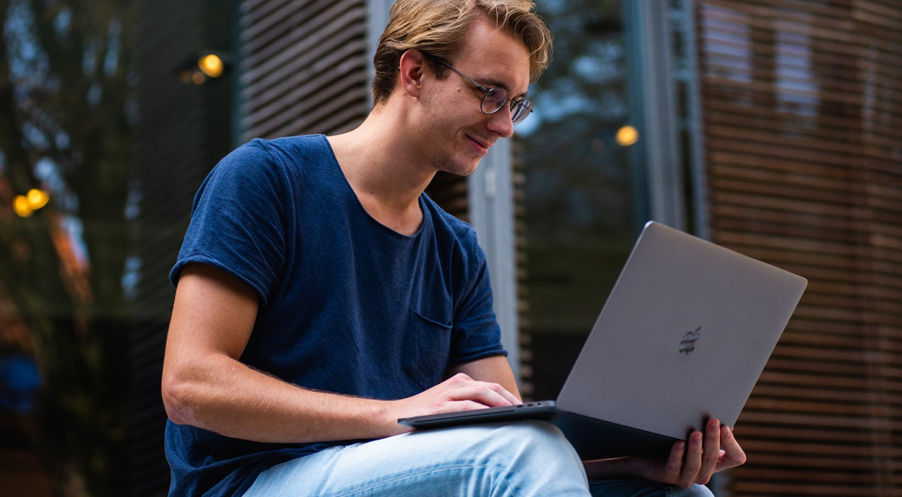 Young male investor looking at laptop