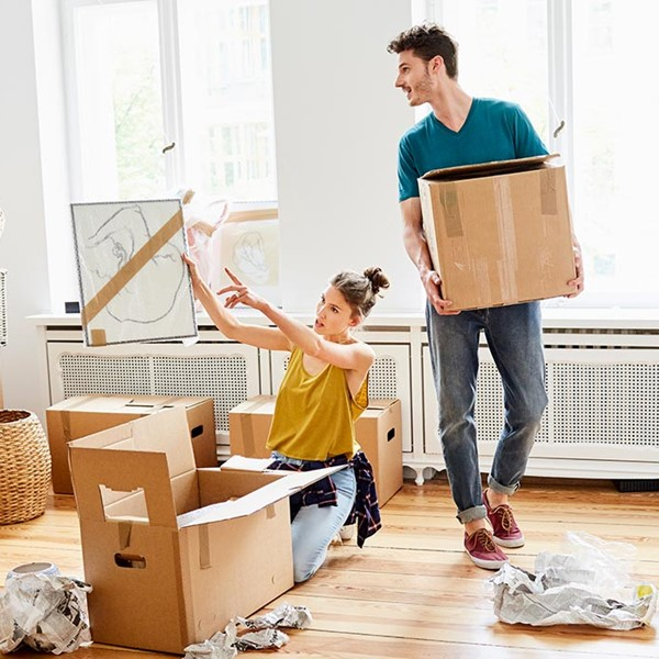 Young couple unpacking boxes in new home
