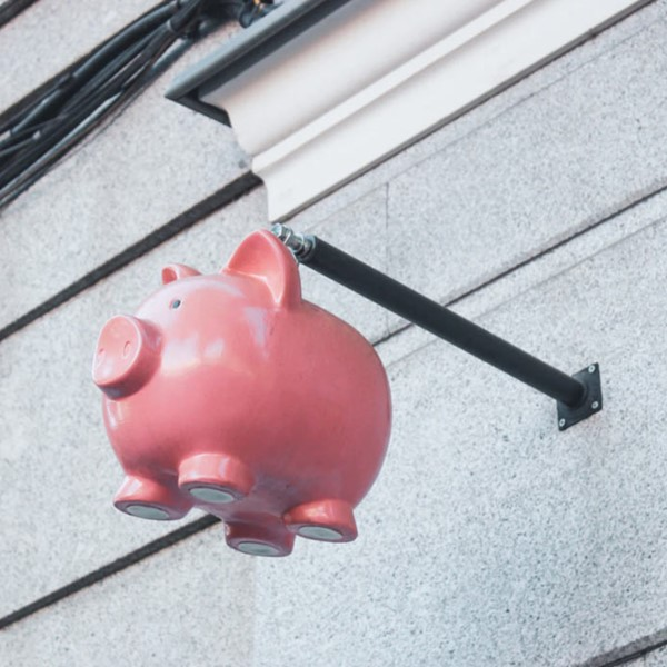Pink piggy bank hanging off side of the building