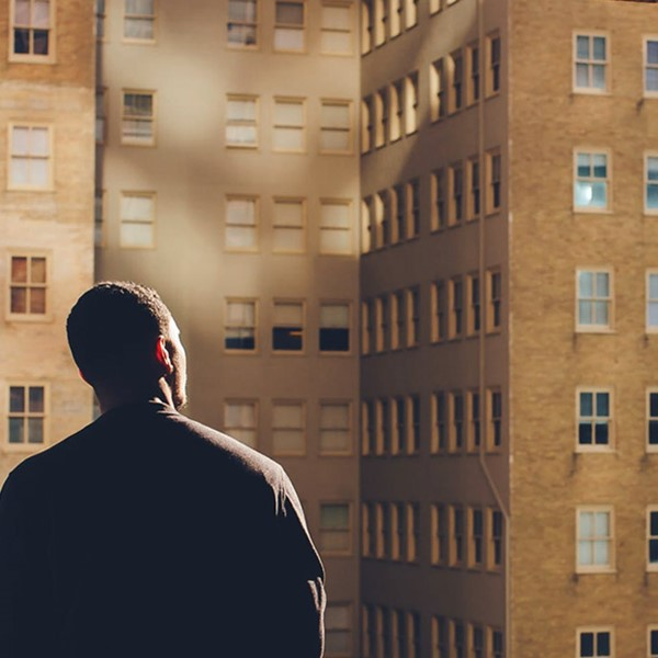 Back of man, looking at buildings across the road