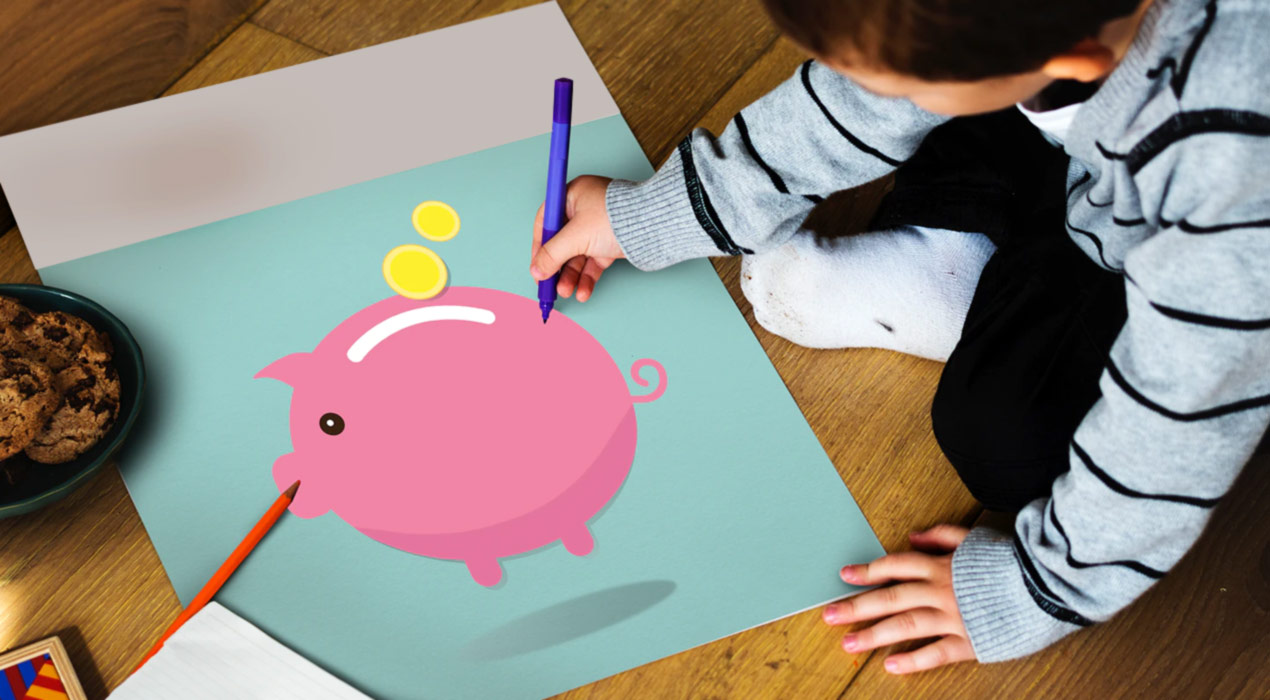 Child drawing on picture of piggy bank on a wooden floor