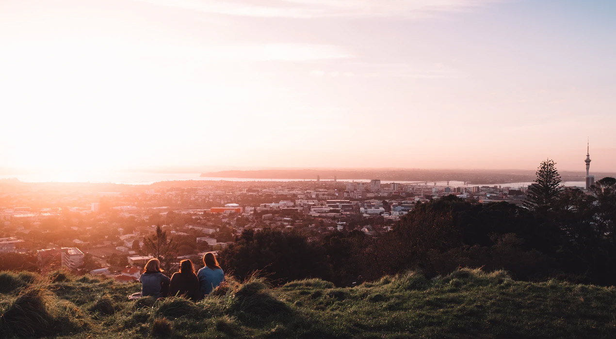 View of Auckland from top of Mt Eden, sun setting with three people in foreground