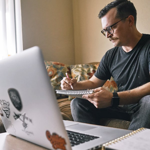 Man in black T-shirt and jeans sitting on couch, holding pad of paper in front of laptop