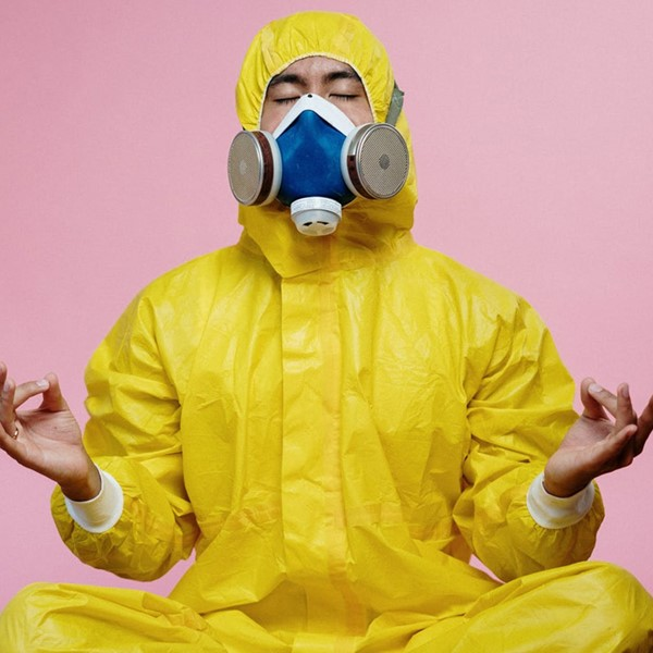 Man in yellow boiler suit and gas mask, meditation