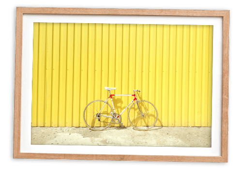 Bike leaning up against yellow wall