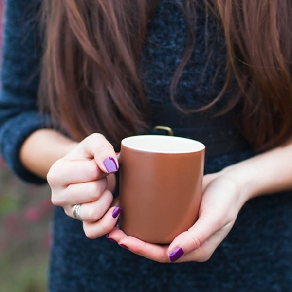 Woman holding warm mug outside