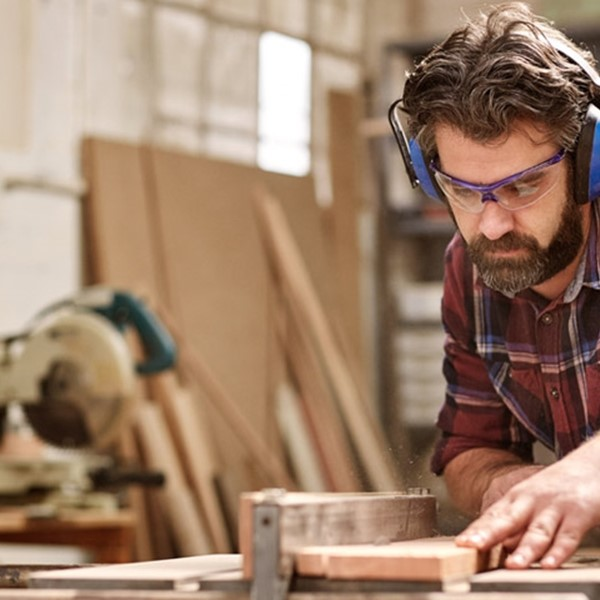 Builder with earphones, sawing