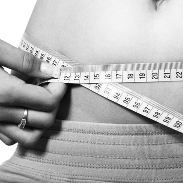 Fitness goals, measuring stomach with tape