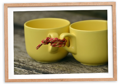 Two yellow cups tied together with string