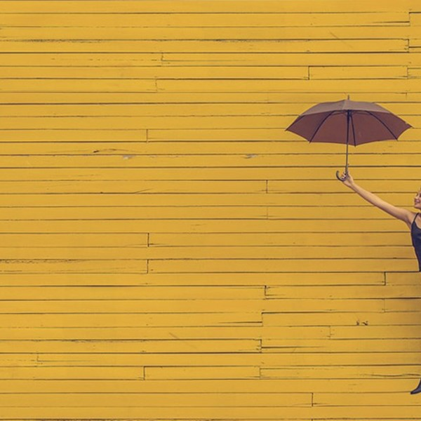 Woman holding umbrella against yellow background