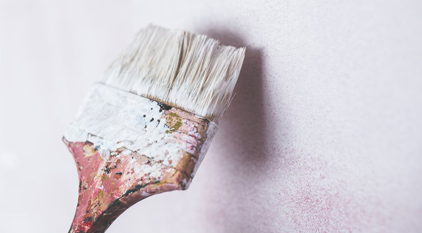 Paint brush with white paint, renovation