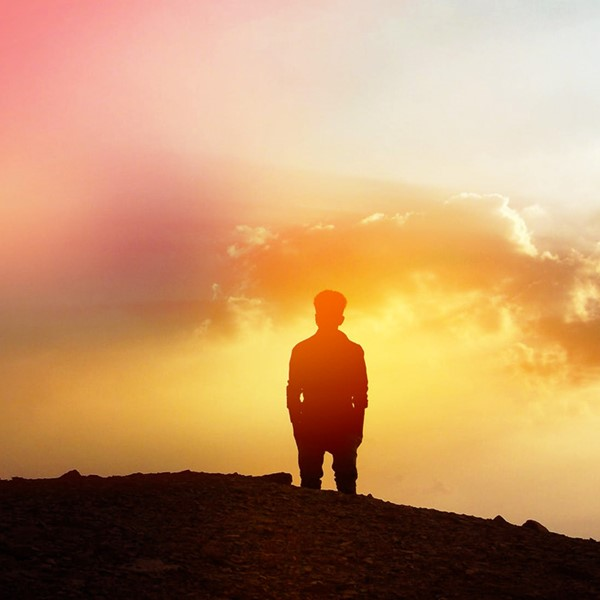 Man standing on mountain looking at the clouds and fog in the distance