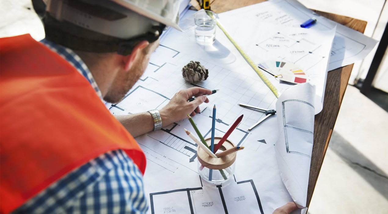 Man wearing hard hat looking over construction drawings on desk
