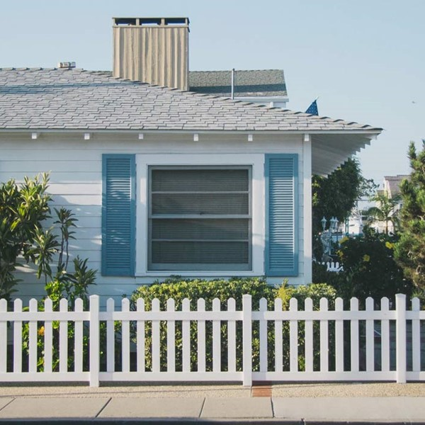 Weatherboard house, sitting behind white picket fence