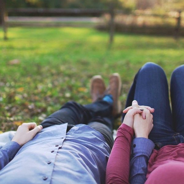 Couple lying on the grass, holding hands