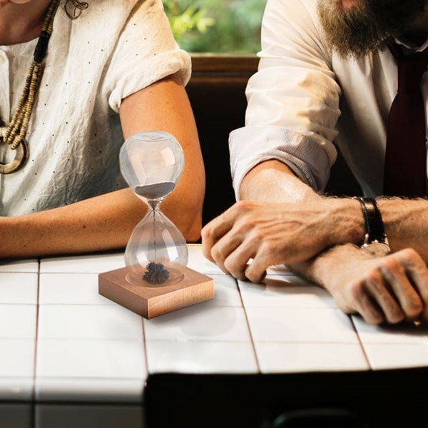Couple sitting at table with hour glass