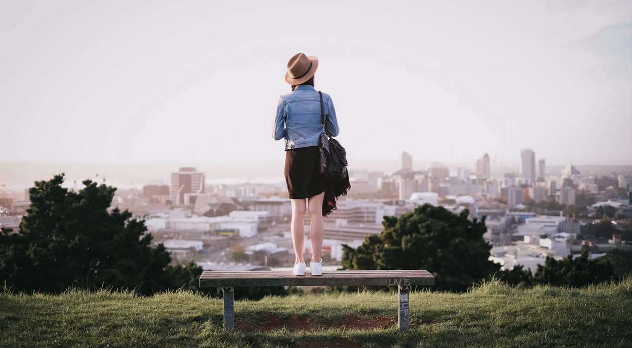 Woman standing on bench on top of hill, looking out at Auckland in the distance