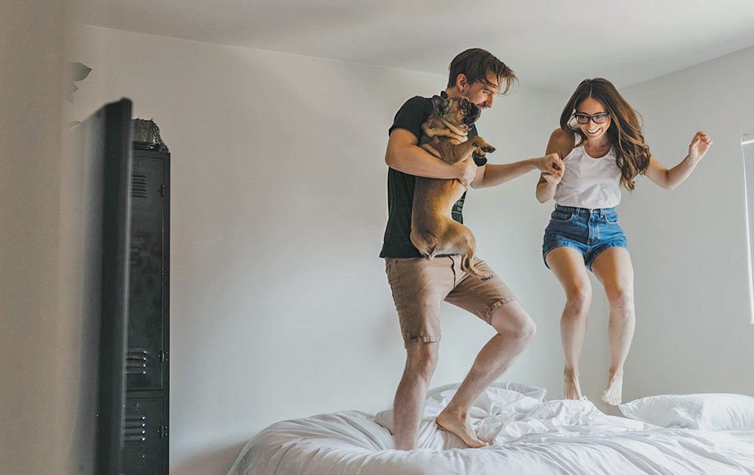 Young couple, jumping on bed laughing and holding dog