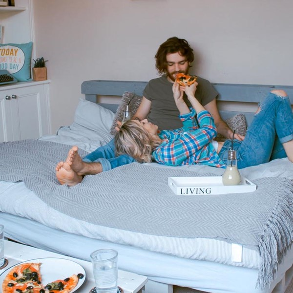 Young couple in their home, lying on bed eating pizza