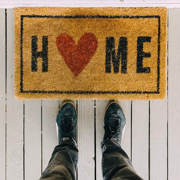 Top view of person's shoes in front of doormat with word 'Home'