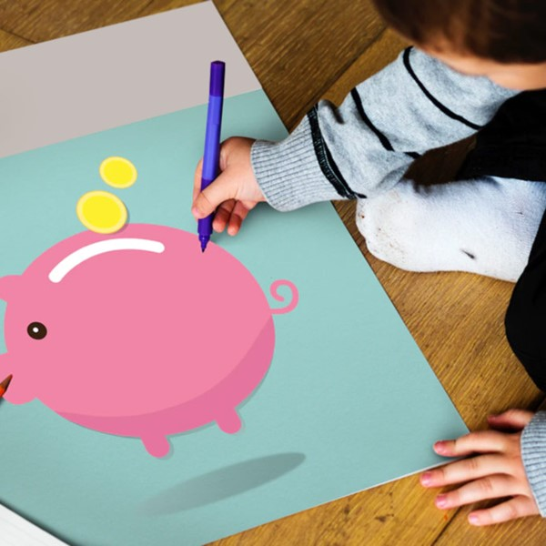 Child drawing on picture of piggy bank