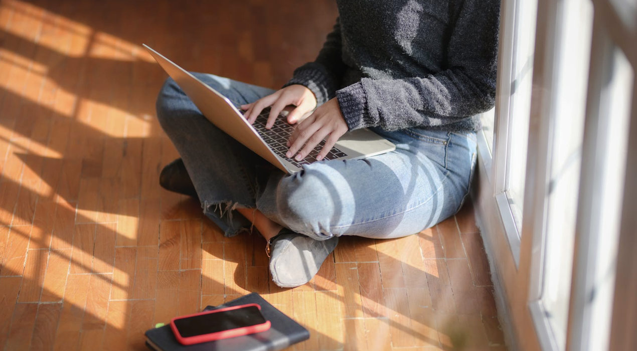 Woman in grey jumper and jeans sitting on floor of home using laptop