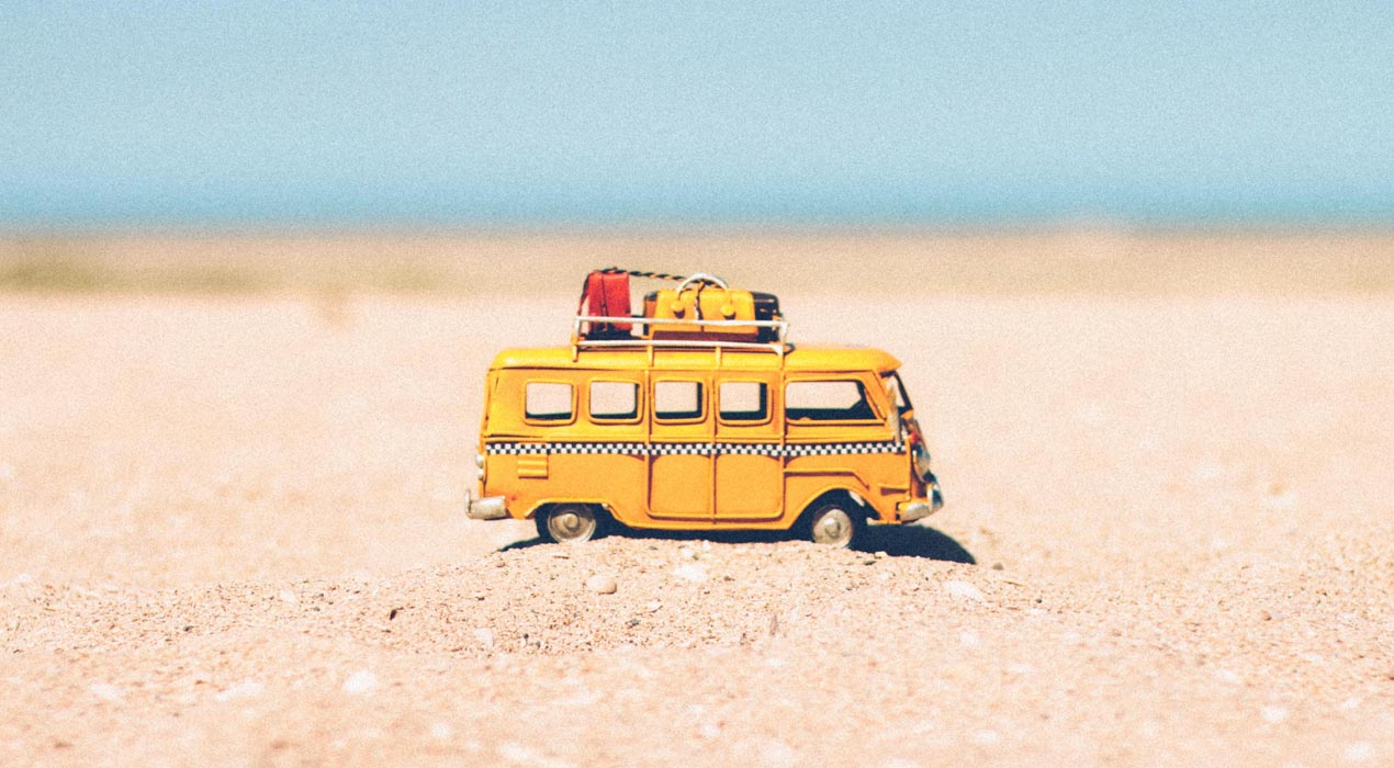 Toy bus on a beach, going on holiday
