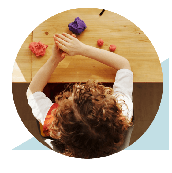 Top view of child playing with playdough at table