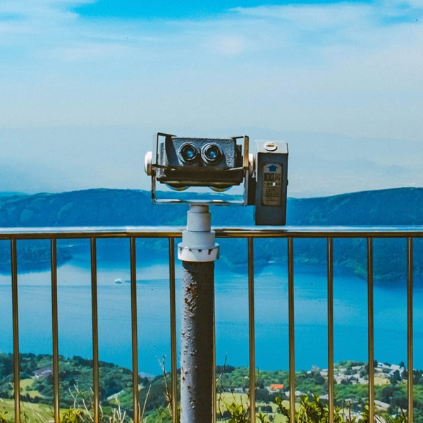 Binoculars next to rail, facing town by an ocean