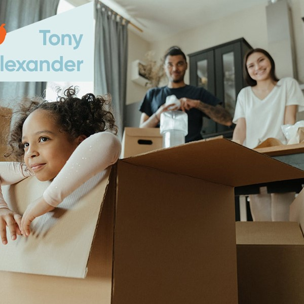 Family in house, cardboard boxes with child in the foreground