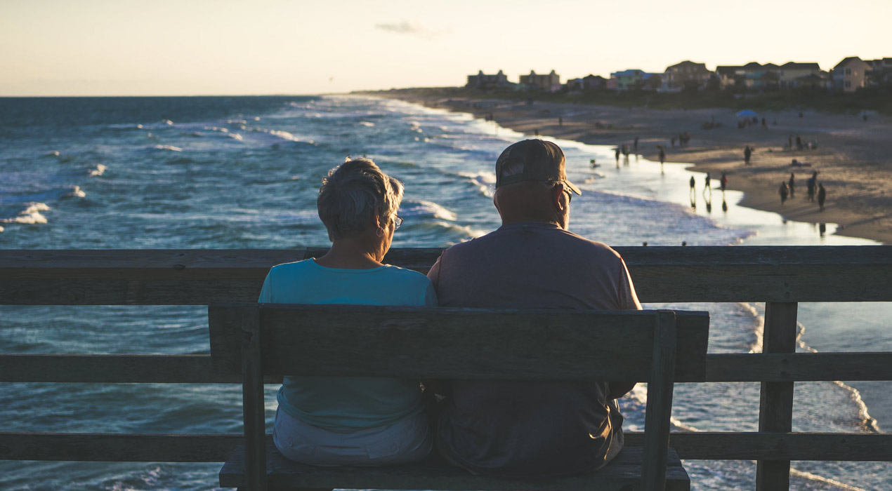 Back of middle aged couple sitting on bench looking at beach