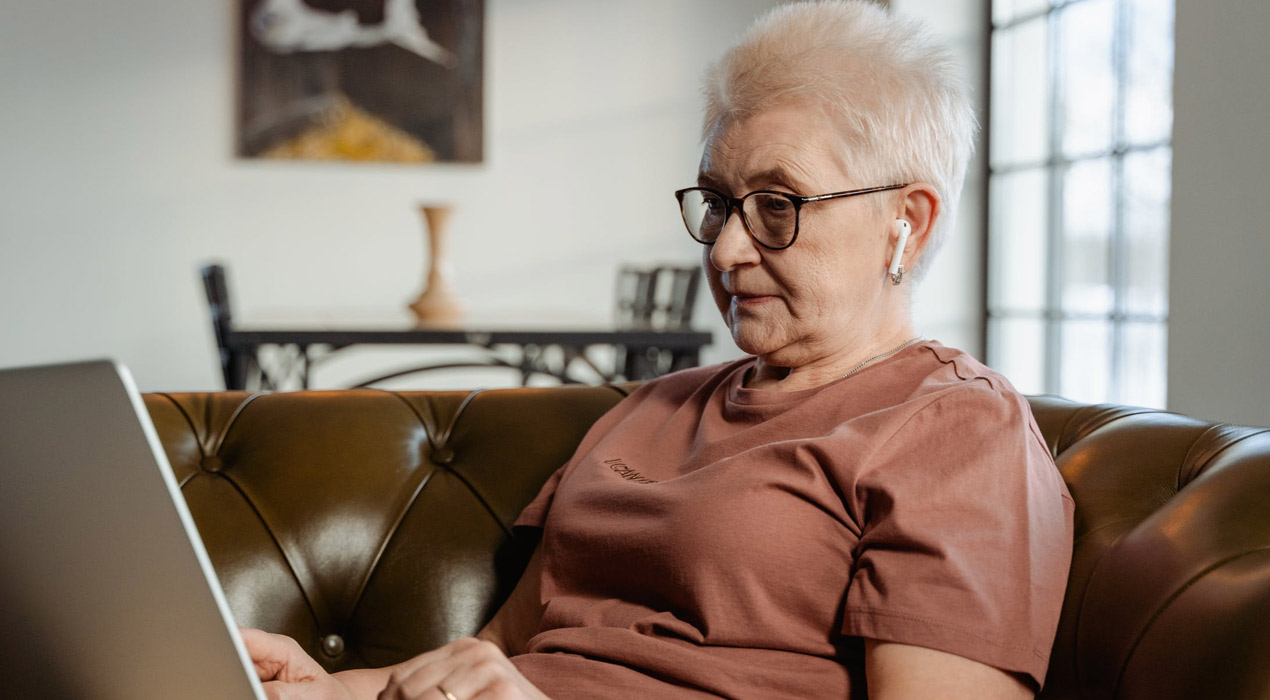 Elderly woman sitting on leather couch looking at laptop