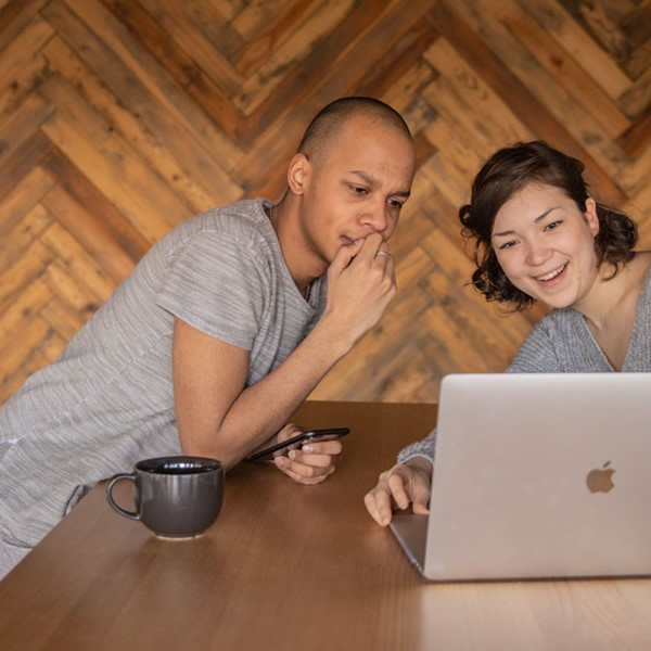 Young guy and woman sitting at table looking at laptop